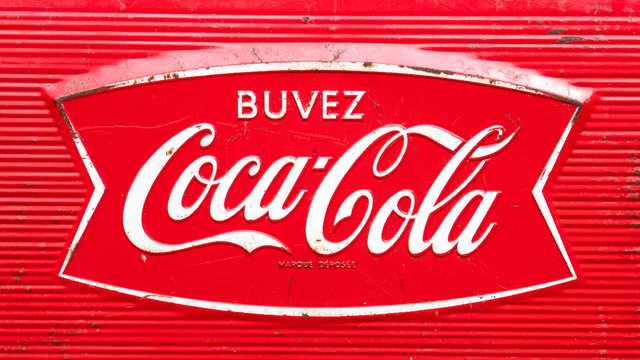 Vintage retro Buvez Coca-Cola trademark logo of the American soft drink brand for French-Canadians, as printed on an antique 1960's era metal cooler.