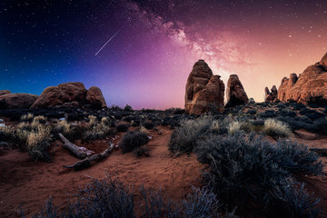 The desert landscape under a mystical violet night sky in Arches National Park near Moab, Utah, USA.
