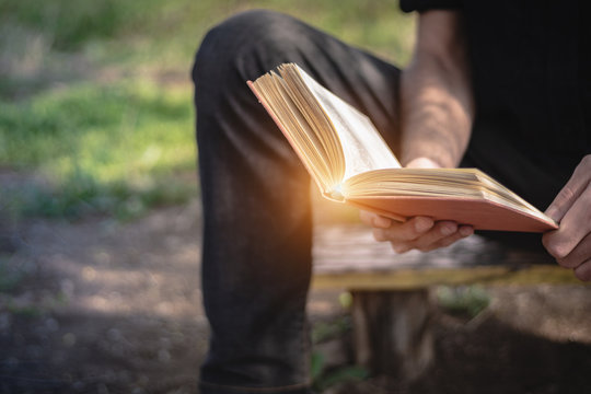 Man sitting on a bench and reading a book outside in the park. Male hands holding a book outdoor. Student studying in nature, focus on the book, copy space for text.