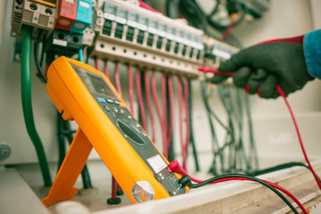 Engineering used a multimeter to measure the voltage of electrical wires produced from solar energy to confirming systems working normally and check for damage to other devices Wall mural