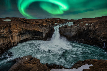 Aurora borealis over Aldeyjarfoss in the Icelandic highlands during night. Traveling and Icelandic landscapes concept.