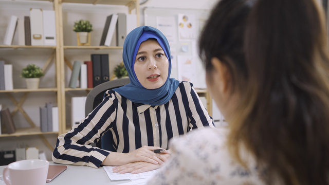 Attentive muslim businesswoman listening to chinese business partner talking during negotiations. multi ethnic people team discuss project. islam financial adviser consulting client meeting in office