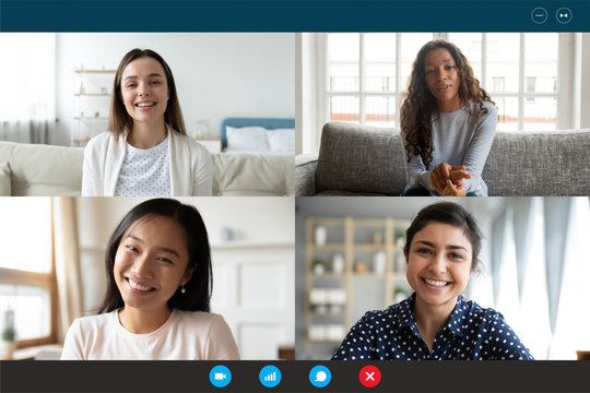 Laptop screen webcam view four multi ethnic beautiful millennial women involved in group video call. Meeting of friends on-line, colleagues working distantly, virtual communication modern tech concept