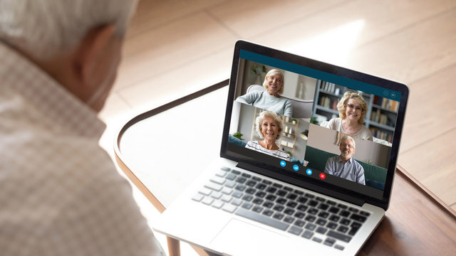 Older generation and modern technologies for virtual visual communication concept. Old man makes videocall talking with relatives or friends by video conference app, pc screen view over male shoulder