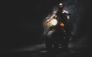 Moto rider on the dark empty road