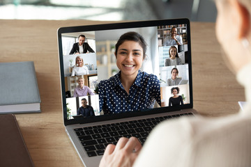 Laptop screen over woman shoulder view, indian businesswoman leading videoconference distant communication group videocall conversation. Diverse friends using modern tech enjoy virtual meeting concept Wall mural