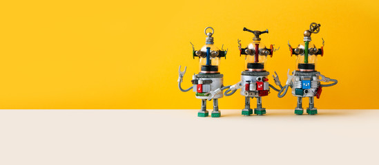 Garden Poster UFO Three funny alien ufo robots, yellow wall background. Sky fi mechanical fantasy characters with arms springs metal torsos, glass heads. Copy text