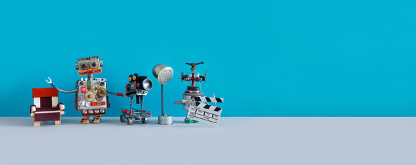 Robotic filmmaking backstage concept. Two robots shoots motion picture television episode or movie. Funny filmmakers director cameraman, cyborg assistant clapperboard on blue background, copy space