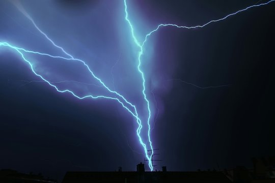 Low Angle View Of Lightning Over Houses Against Sky At Night