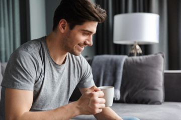 Man indoors at home drinking coffee. Wall mural