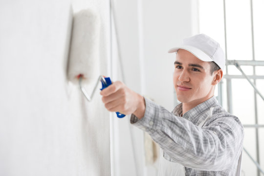 Friendly young male painter painting a wall