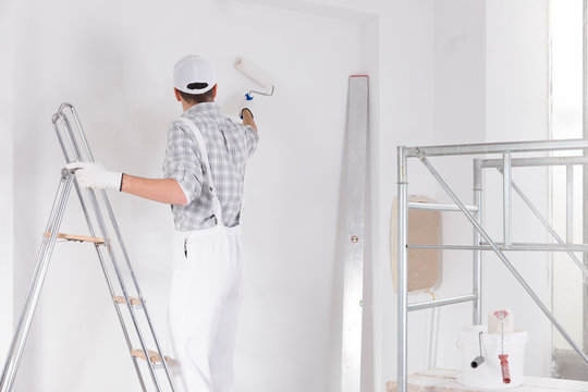 Painter standing on a ladder painting a white wall