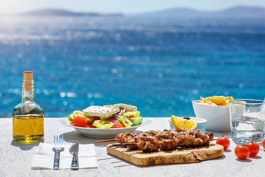 Greek food concept with farmers salad and souvlaki skewers in front of the sparkling, blue Aegean sea during summer time