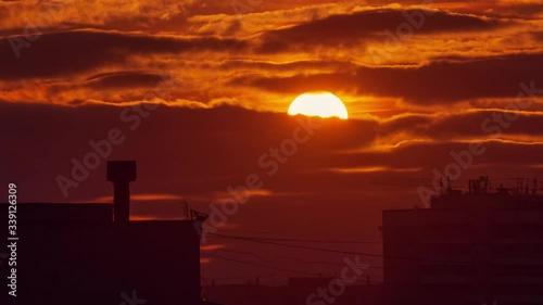 Fotobehang Beautiful orange sunset sun clouds moving in sky over dark city skyline silhouette. Timelapse, 4K UHD