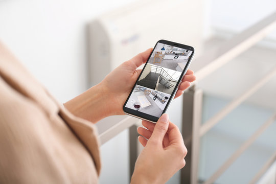 Woman monitoring modern cctv cameras on smartphone indoors, closeup. Home security system