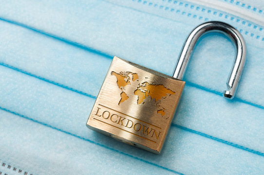 Coronavirus world lockdown end: a lock with a world map and the word lockdown engraved on a light blue surgical mask.