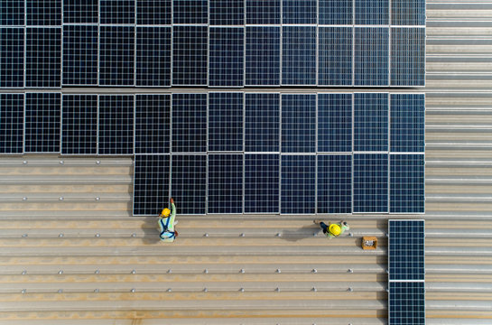 top view worker installing a solar cell on the factory roof.
