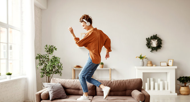 Cheerful woman listening to music and dancing on soft couch at home in day off.