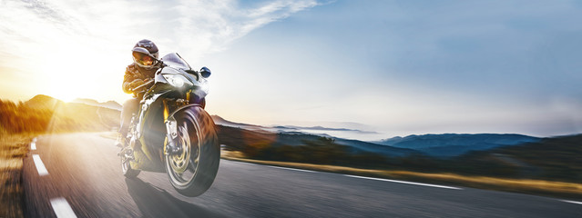 Wall Mural - Fast motorbike on the coastal road riding. having fun driving into the sunset