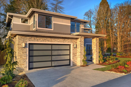 Modern contemporary house exterior with luxury details, landscaping, stone, wood, glass, lots of large windows.