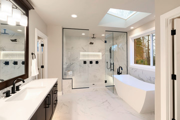 Luxury modern home bathroom interior with dark brown cabinets, white marble, walk in shower, free standing tub.