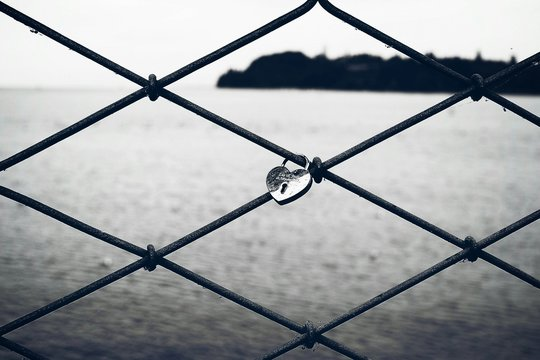 Close-up Of Heart Shape Padlock Tied Up On Chainlink Fence By Sea Against Sky