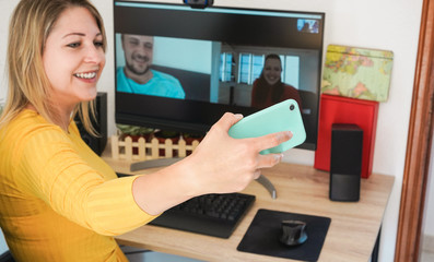 Young woman chatting with friends doing video call while taking selfie photos with mobile phone - Alternative meeting during home isolation quarantine - Focus on hand