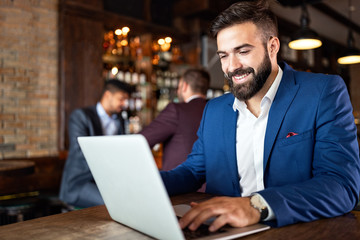 Handsome business man using laptop at his work break in restaurant Wall mural