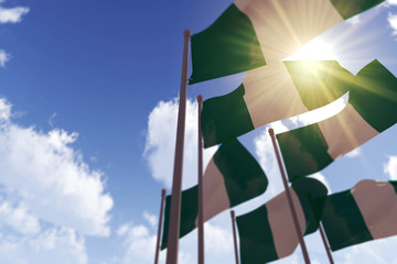 Nigeria flags waving in the wind against a blue sky. 3D Rendering