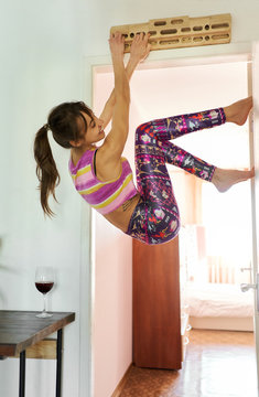 Ahtletic young woman having fun and training at home during quarantine, female climber on campus board in living room.