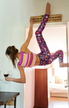 Ahtletic beautiful woman climber having fun at home, hanging on campus board, holding glass with wine in living room.