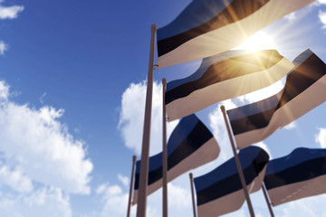 Estonia flags waving in the wind against a blue sky. 3D Rendering