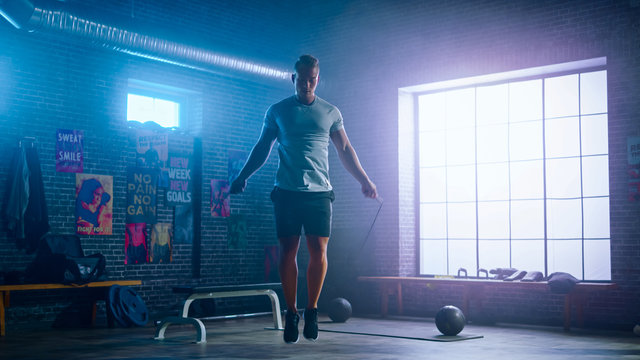 Masculine Athletic Young Man Exercises with Jumping Rope in a Loft Style Industrial Gym. He's Doing His Intense Cross Fitness Training Program. Facility has Motivational Posters on the Wall.