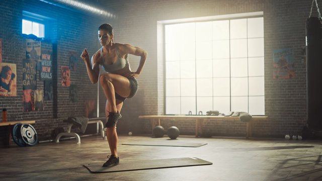 Strong and Fit Beautiful Athletic Woman in Sport Top and Shorts is Doing March and Twist Exercises in a Loft Style Industrial Gym with Motivational Posters. It's Her Cross Fitness Training Workout.