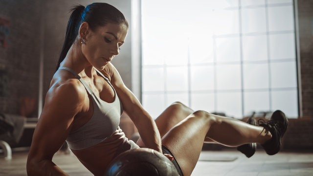 Close Up of a Strong and Fit Athletic Woman in Sport Top Doing Core and Ab Exercises with Ball in a Loft Style Industrial Gym with Motivational Posters. It's Part of Her Cross Fitness Training Workout