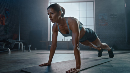 Strong and Fit Athletic Woman in Sport Top and Shorts is Doing Push Up Exercises in a Loft Style Industrial Gym with Motivational Posters. It's Part of Her Cross Fitness Training Workout.
