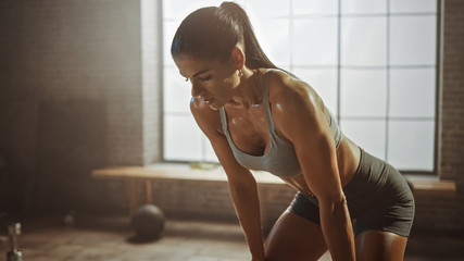 Portrait of a Beautiful Strong Fit Brunette Wiping Sweat from Her Face in a Loft Industrial Gym with Motivational Posters. She's Catching Her Breath after Intense Fitness Training Workout. Warm Light.