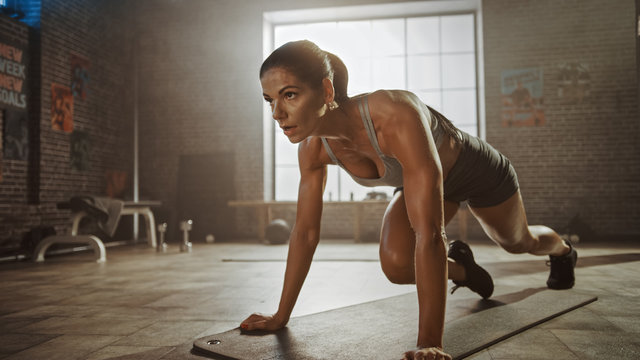 Strong and Fit Athletic Woman in Sport Top and Shorts is Doing Mountain Climber Exercises in a Loft Style Industrial Gym with Motivational Posters. It's Part of Her Cross Fitness Training Workout.