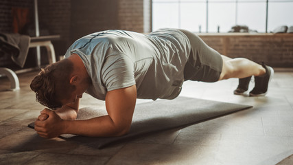 Strong Masculine Male is Holding a Plank Position in Order to Exercise His Core Strength. Man is Exhausted and Struggling with Training. Workout in a Loft Gym.