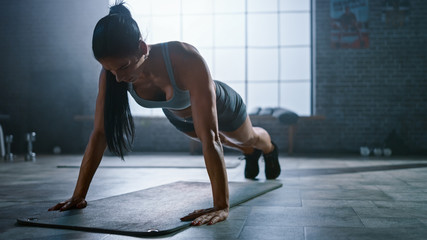 Strong and Fit Athletic Busty Woman in Sport Top and Shorts is Doing Push Up Exercises in a Loft Style Industrial Gym with Motivational Posters. It's Part of Her Cross Fitness Training Workout.