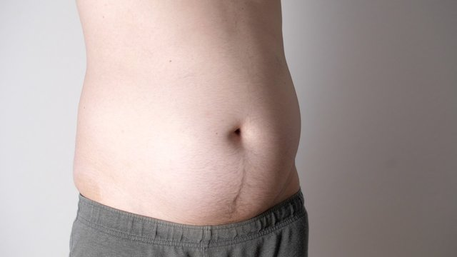 Fat male  stomach. Weight loss or weight gain during quarantine. Attractive man with tattoos with obese bare belly. Close-up of male beer belly of sexy man. Bodypositive