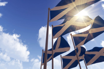 Scotland flags waving in the wind against a blue sky. 3D Rendering