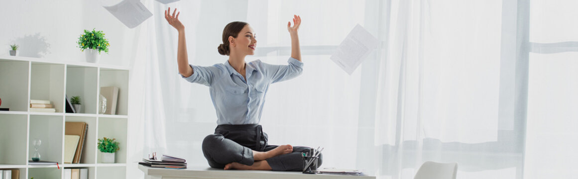 panoramic shot of happy businesswoman sitting in lotus pose on table with falling business papers in office