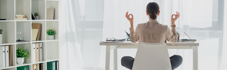 panoramic shot of businesswoman meditating in lotus pose with gyan mudra at workplace with incense...
