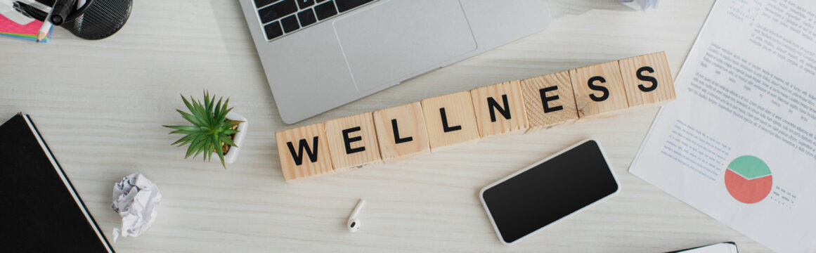panoramic shot of business workplace with earphones, laptop, smartphone and alphabet cubes with wellness word