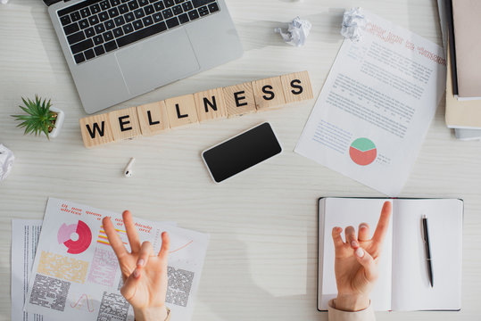 cropped view of businesswoman making surya mudra at workplace with documents, laptop, smartphone and alphabet cubes with wellness word