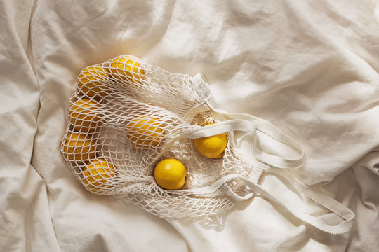 Cotton net bag with lemons lying on the bed. Sustainable lifestyle.