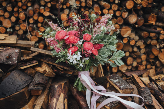 Wedding floristry. A bouquet of red and white flowers with greenery and a pink ribbon lies on the wood