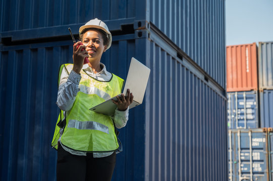 Black foreman woman worker working checking at Container cargo harbor holding laptop and radio to loading containers. African dock female staff business Logistics import export shipping concept.