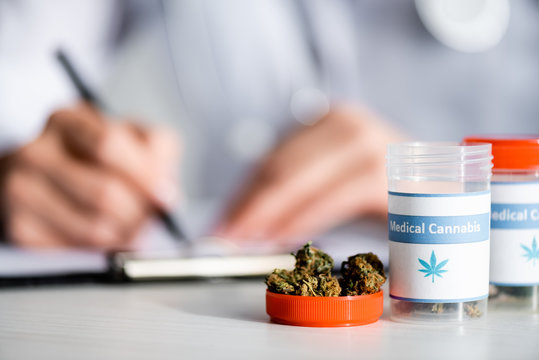 selective focus of dried weed and bottles with medical cannabis lettering near doctor writing prescription
